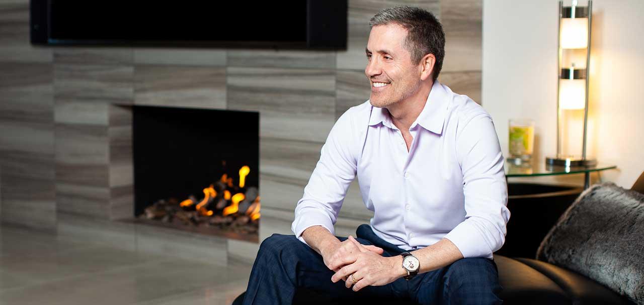Foudner, Robert Altshuler, sitting in home wearing watch